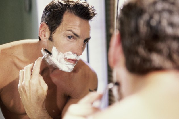 Close-up of a young man shaving in the bathroom