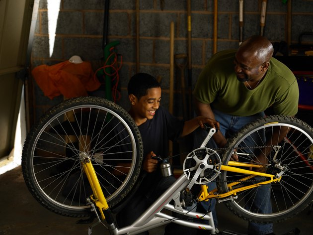 Father and teenager oiling bicycle chain