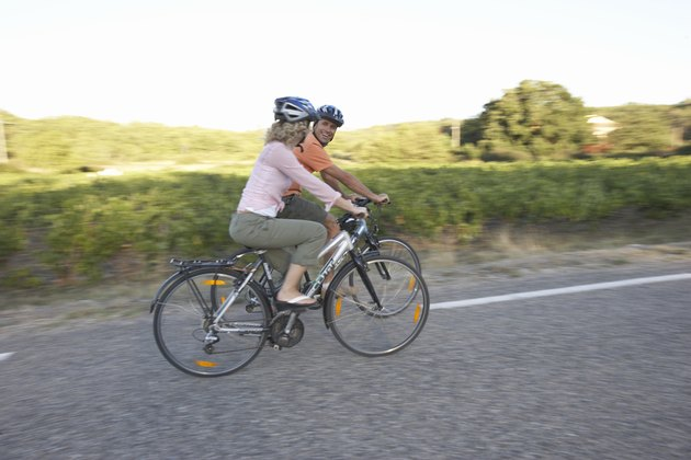 Woman and man riding bicycles on country road, side view
