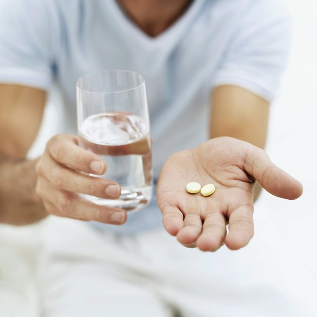 close-up of a person holding pills and a glass of water
