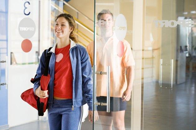 Woman and man walking through gym doors