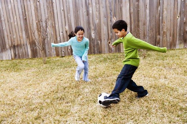 Children ( 8-11)  playing football in ground