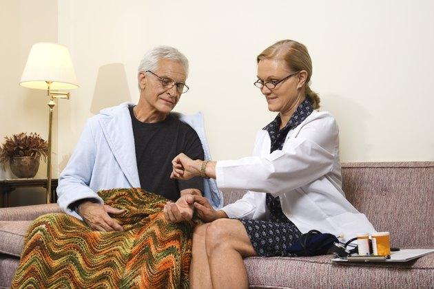 Doctor checking elderly man's heart rate