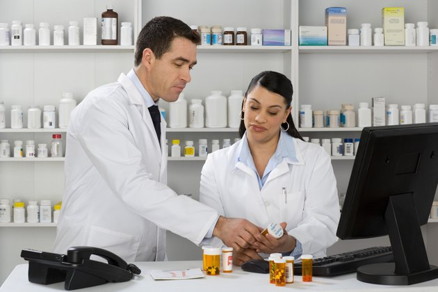 Pharmacists at a computer with medication and talking