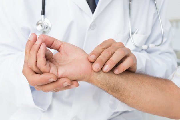 Mid section of a doctor taking a patients pulse