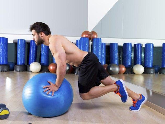 Fitball abdominal push ups Swiss ball man one single leg pushup at fitness gym