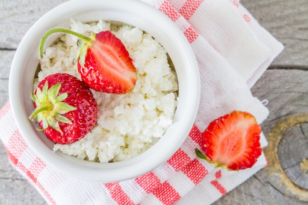 Cottage cheese in white bowl with strawberries, plaid napkin