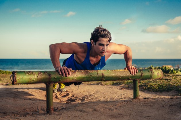 brazilian musculated man doing push-ups at beach