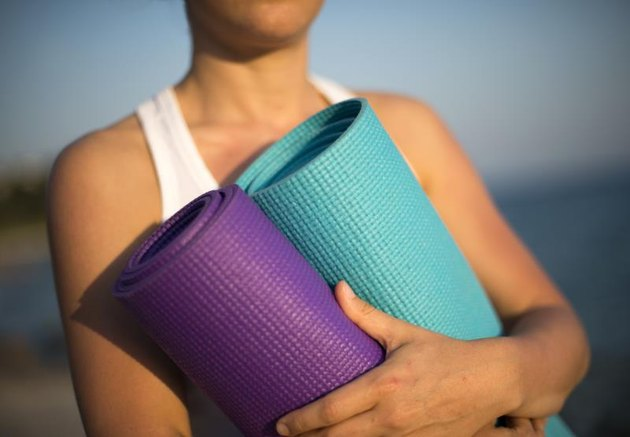 Unrecognised lady holds two yoga mats in natural backround.