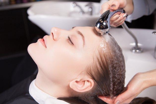 Hairdresser washing a woman's blond hair