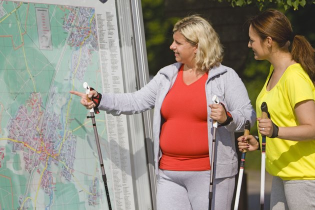 Two friends holding hiking poles and looking at map