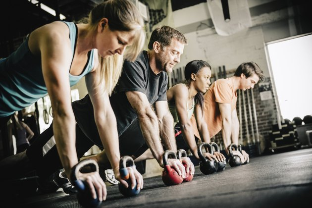 People doing a HIIT workout using kettlebells in a gym