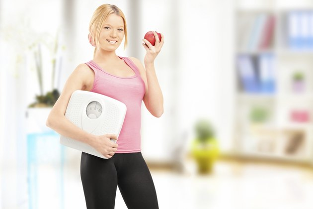 Young smiling female holding a weight scale and an apple