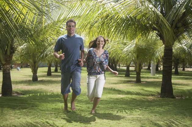 Young couple running among palm trees, holding hands