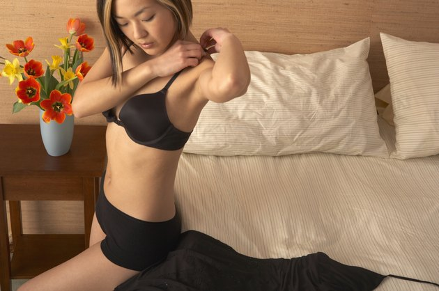 High angle view of a young woman putting on her cloths