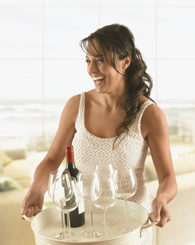 Hispanic woman carrying tray of wine and glasses