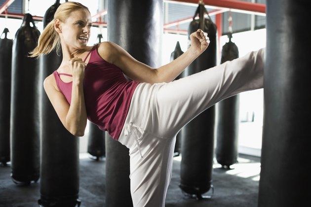 Blonde woman kicking punching bag