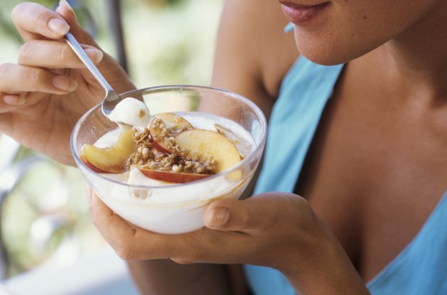 Young woman eating yoghurt with nectarines and nuts