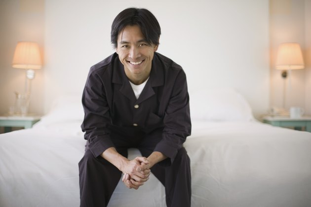 Smiling man sitting on edge of bed