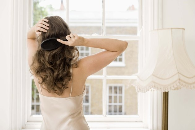 Rear view of woman brushing hair