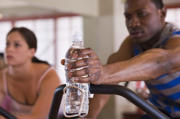 Man reaching for bottled water on exercise bike