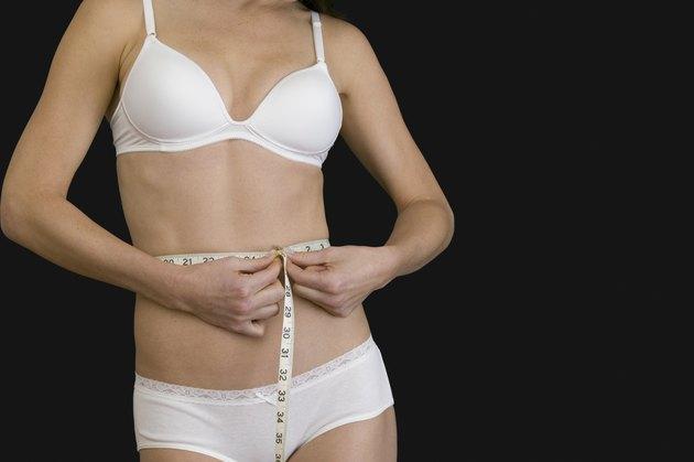 Woman in lingerie measuring waist