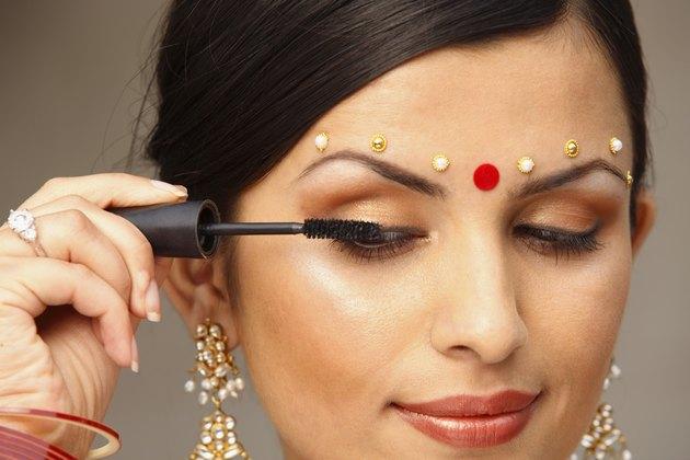 Woman with traditional bindi applying makeup