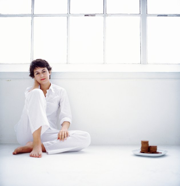 portrait of a woman sitting on the floor beside a plate of cookies