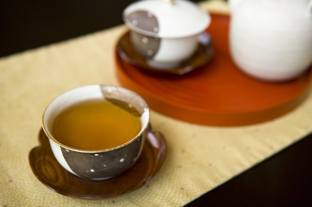 Tea pot and two cups of green tea on table, high angle view, close up, black background, Japan