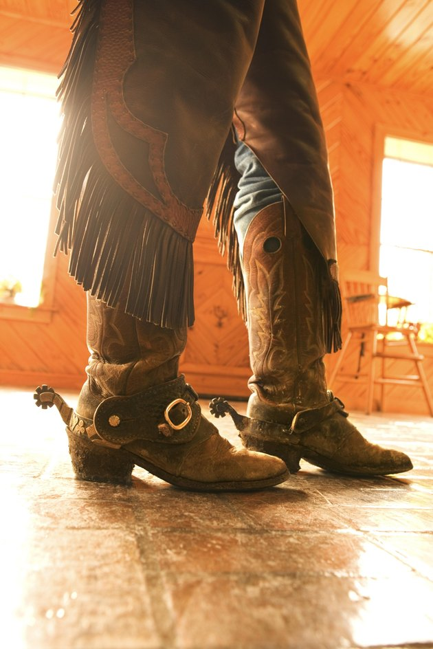Boots and spurs with chaps on legs of cowboy