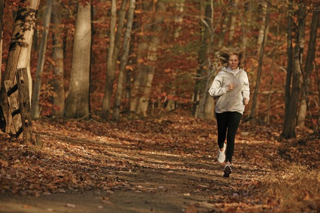 Woman jogging on trail in autumn forest