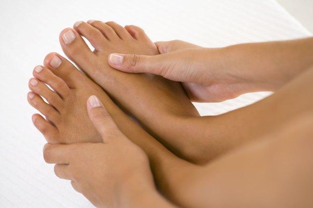 Hands massaging bare feet
