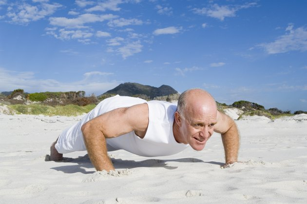 Mature man doing pushups on beach