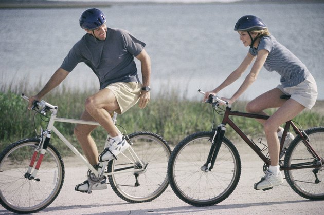 Side profile of a mature couple cycling on the road