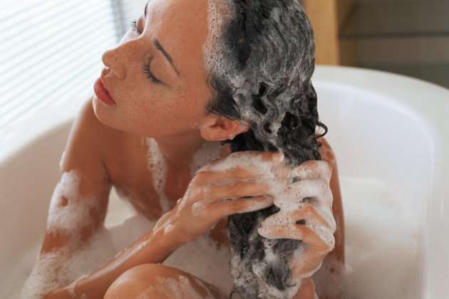 Woman washing hair in bubble bath