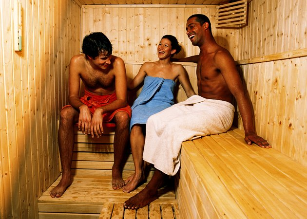 Two young men and a young woman sitting in a sauna together laughing