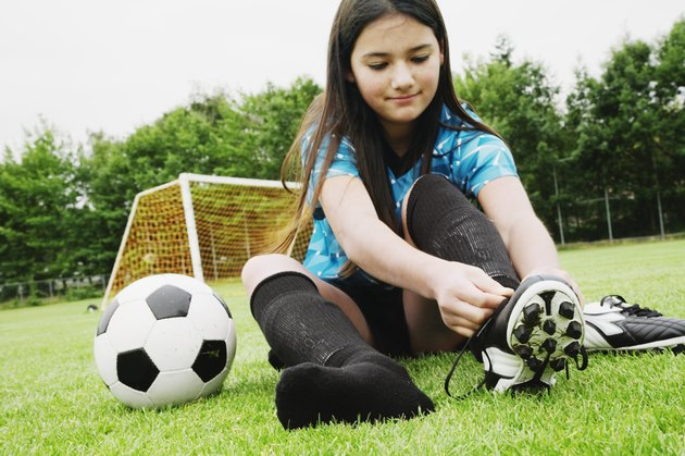 Girl tying soccer cleat