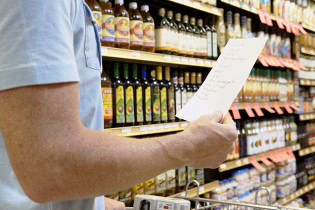 Man with shopping list in supermarket, mid section