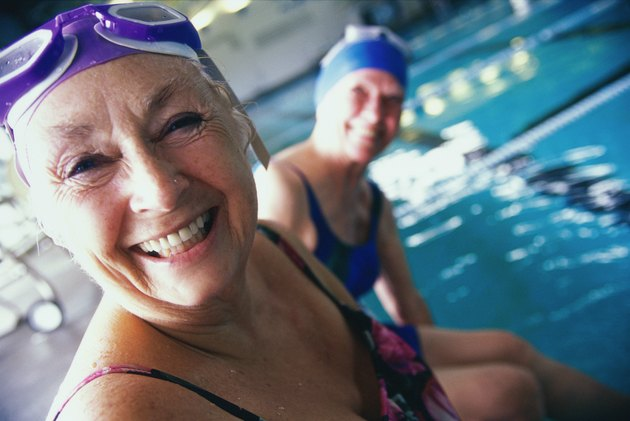 Portrait of two senior women sitting at the edge of a swimming pool