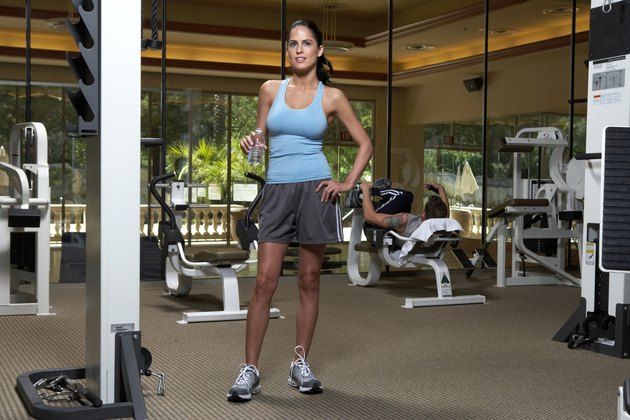 Woman with water bottle standing in gym