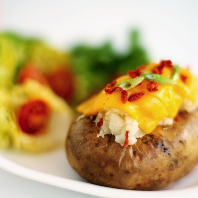 Close-up of salad and a baked potato with cheese and chives