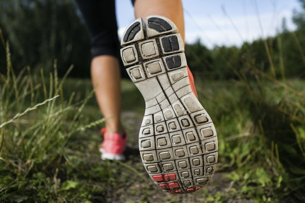 Woman and running shoes in forest, exercising outdoors