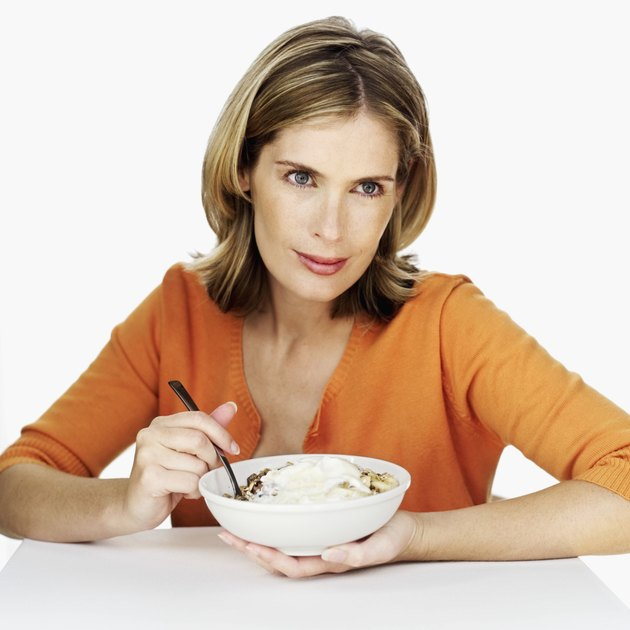Portrait of a young woman holding a bowl of cereal and a spoon