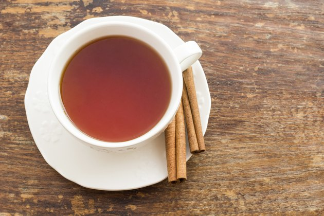 Cup of tea with cinnamon on a wooden surface