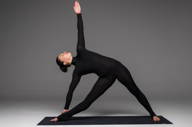 Trikonasana. Beautiful yoga woman practice yoga poses on grey background. Yoga concept.