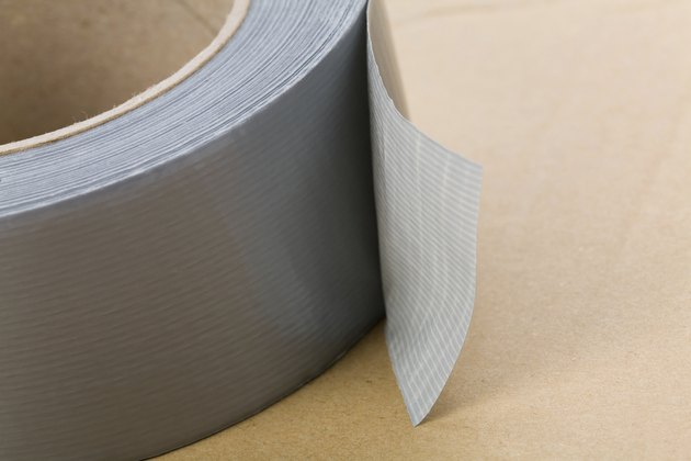 A roll of grey duct tape on a brown surface