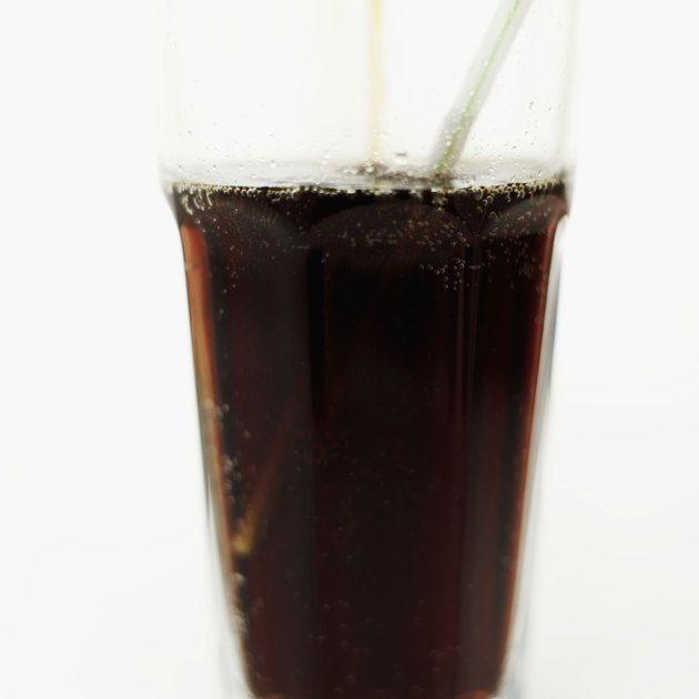 Close-up of a glass of a cola with a straw