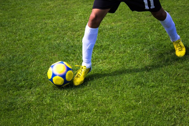 Low section of soccer player carrying ball in soccer field