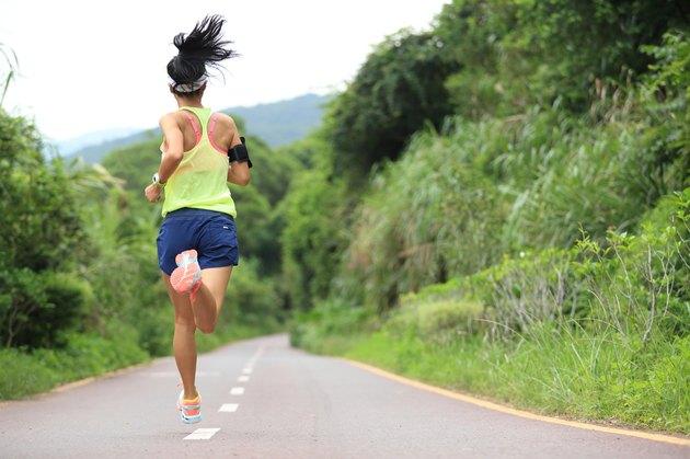 trail runner athlete running on forest trail.
