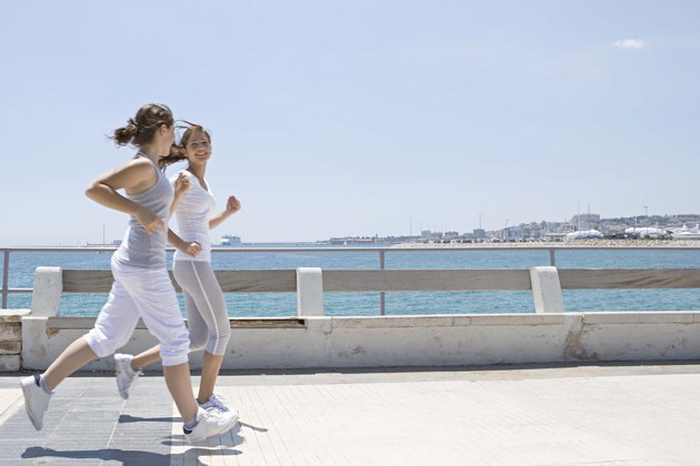 Teenage girls running on sidewalk by ocean